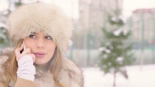 vidéos et rushes de belle femme avec le chapeau de fourrure utilisant le smartphone dans le stationnement d'hiver dans la ville pendant la journée dans le temps neigeux avec la neige tombante - manteau et blouson d'hiver