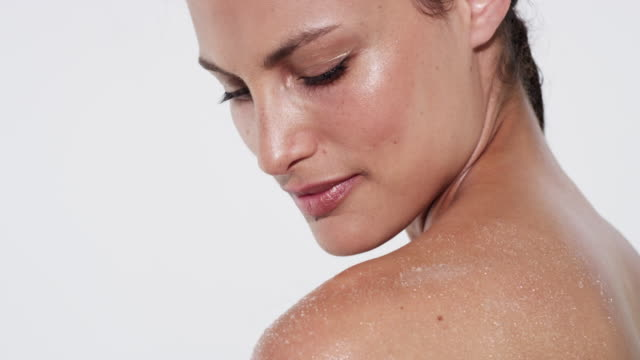 vídeos de stock e filmes b-roll de beautiful woman with glowing skin rubbing salt scrub into the top of her arm/shoulder - esfregar tocar