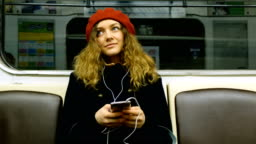 Beautiful woman with headphones uses the phone in the subway