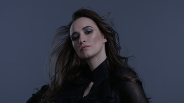 Schöne Frau mit langen schwarzen Haaren zeigt Mimik. Mode video.