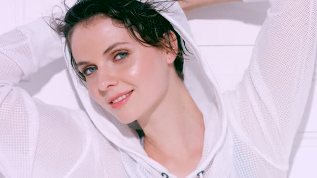 beautiful woman with short brunette hair wearing a white hooded sports top - woman hands behind head stock videos & royalty-free footage