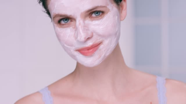 beautiful woman with short brunette hair wearing a white moisturising face mask. - beauty treatment stock videos & royalty-free footage