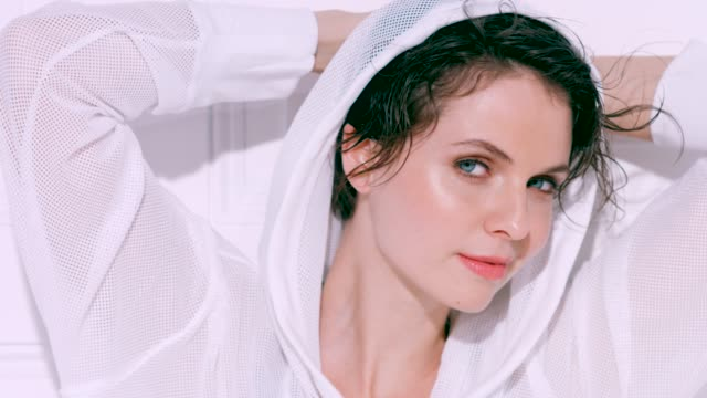 Beautiful woman with short brunette hair wearing a white sports hoody