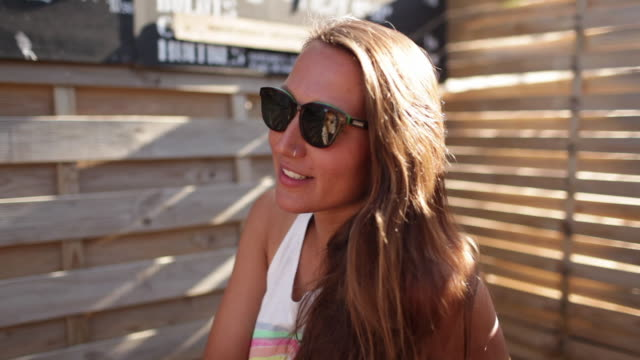 beautiful woman with sunglasses and nose piercing talking to friend in sunshine by beach. - nose piercing stock videos & royalty-free footage