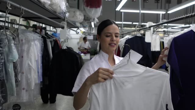 Beautiful woman working at a dry cleaner moving clothes from rack to another smiling