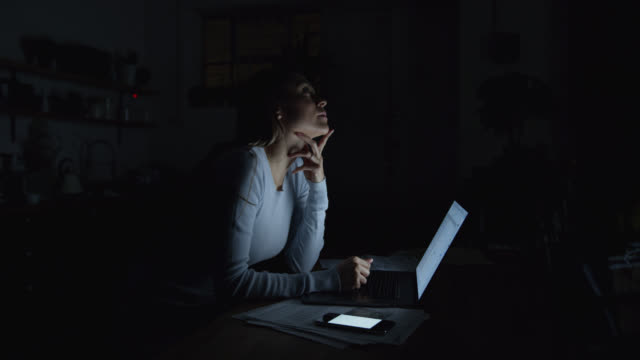 beautiful woman working late at home using a laptop and receiving text messages on smartphone - urgency stock videos & royalty-free footage