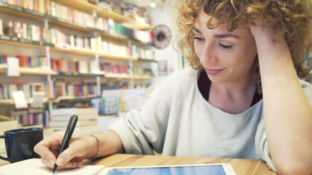 beautiful woman working with a digital tablet in a library-coffee shop. - calendar stock videos & royalty-free footage