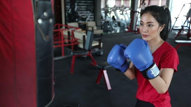 美しい女性アジアのボクサー幸せで楽しいフィットネスボクシングとボクシンググローブを着用して袋を打つ。スローモーション - 殴る点の映像素材/bロール