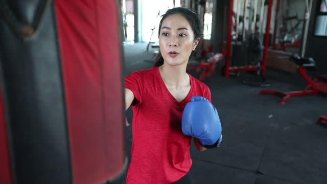 美しい女性アジアのボクサー幸せで楽しいフィットネスボクシングとボクシンググローブを着用して袋を打つ。スローモーション - 汗点の映像素材/bロール