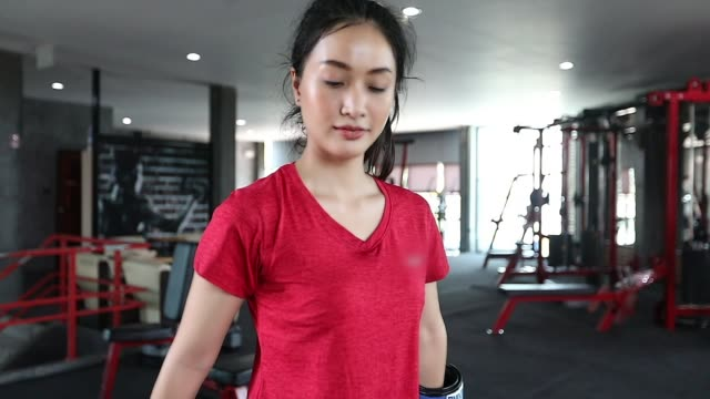 Beautiful women asian boxer happy and fun fitness boxing and Punching A Bag With wearing boxing gloves.slow motion