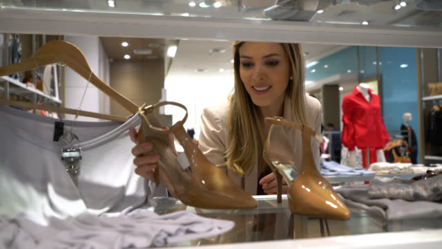 beautiful women at a store looking at a pair of heels she liked - borsetta video stock e b–roll