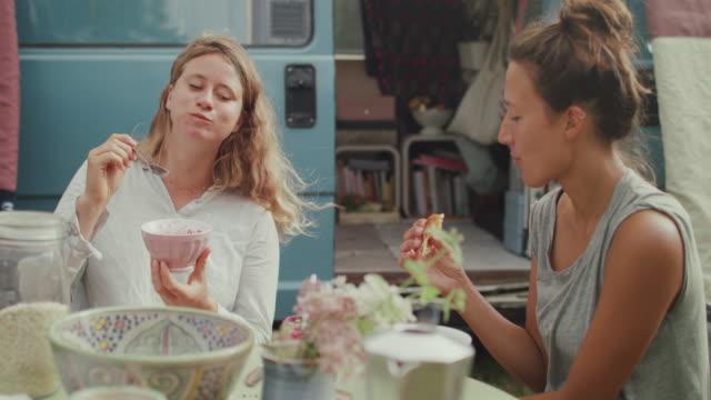 vidéos et rushes de beautiful women eating breakfast in front of van/camping in the morning - céréale