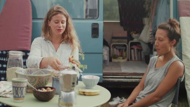 vídeos y material grabado en eventos de stock de beautiful women eating breakfast in front of van/camping in the morning - cereal de desayuno