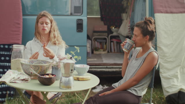 Beautiful women eating breakfast in front of van/camping in the morning