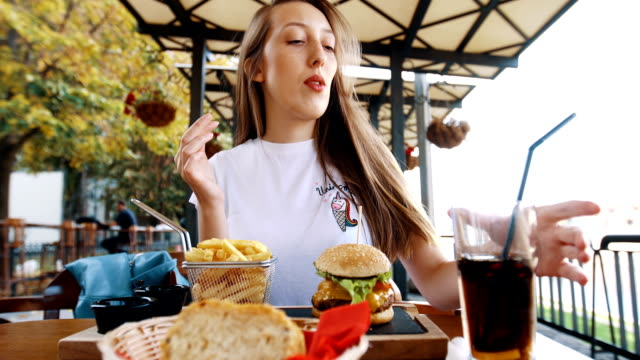 beautiful women enjoy at her fries and drinks - cheeseburger stock videos & royalty-free footage