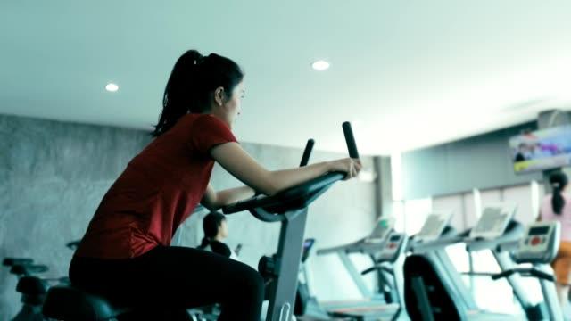 ジム、スローモーションでエクササイズのための美しい女性 - インドアサイクリング点の映像素材/bロール