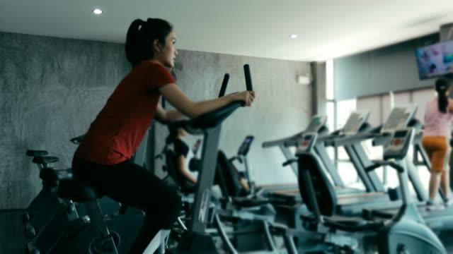 ジムでエクササイズのための美しい女性 - インドアサイクリング点の映像素材/bロール