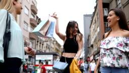 Beautiful women having fun in the city after shopping