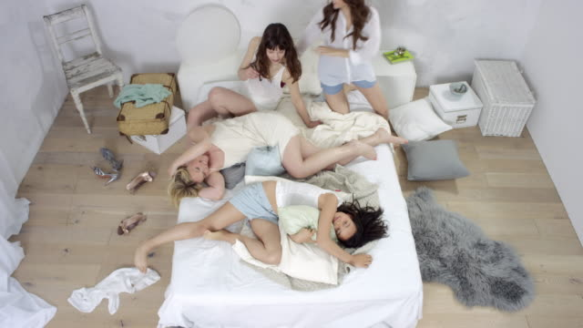 4 beautiful women lying together in bed - coming into frame and lying down on bed / enjoying themselves - reclining stock videos and b-roll footage