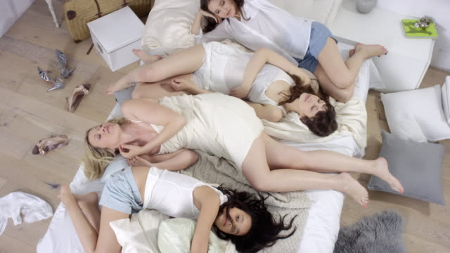 4 beautiful women lying together in bed - coming into frame and lying down on bed / enjoying time together