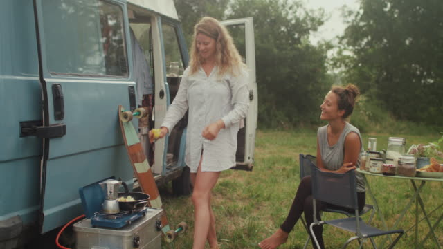 Beautiful women making breakfast in front of a van/camping in the morning