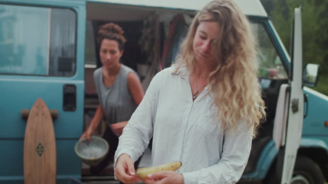 beautiful women making breakfast laughing, eating in front of van/camping in the morning - alles hinter sich lassen stock-videos und b-roll-filmmaterial