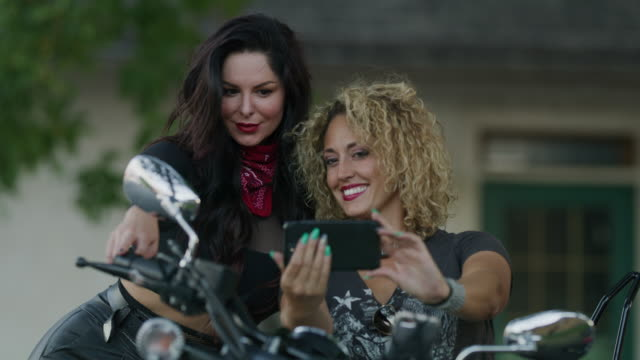beautiful women on motorcycle posing for cell phone selfies / payson, utah, united states - payson stock videos & royalty-free footage