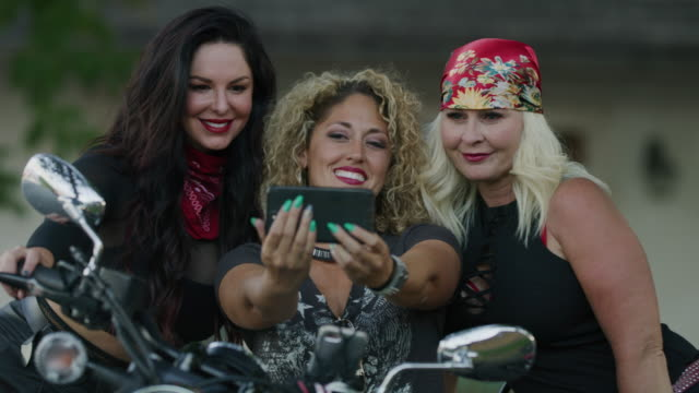 vidéos et rushes de beautiful women on motorcycle posing for cell phone selfies / payson, utah, united states - payson