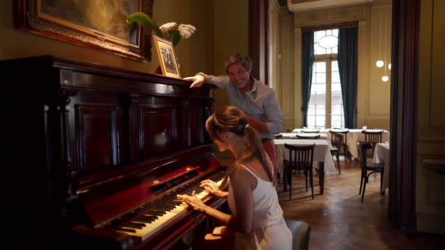 vidéos et rushes de belles femmes jouant du piano pour son mari - être debout