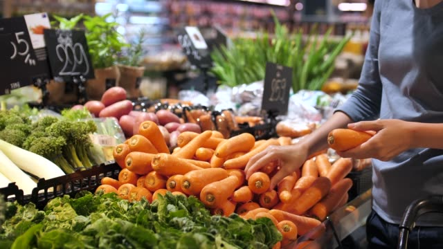 beautiful women shopping carrot vegetables and fruits in supermarket - groceries stock videos & royalty-free footage