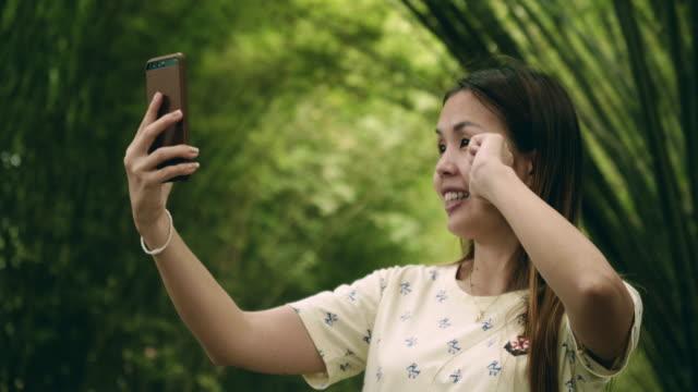 vidéos et rushes de belles femmes prendre la photo avec le smartphone à l'usine de bambou vert - bamboo plant