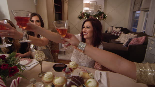 stockvideo's en b-roll-footage met beautiful women toast at a holiday christmas party - martiniglas