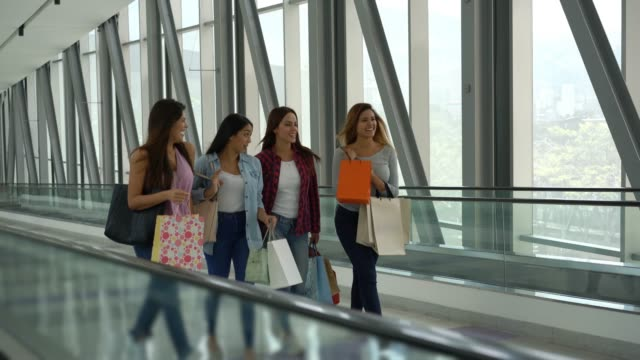 beautiful women walking in between the moving walkways at the mall while talking and smiling - spending money stock videos & royalty-free footage