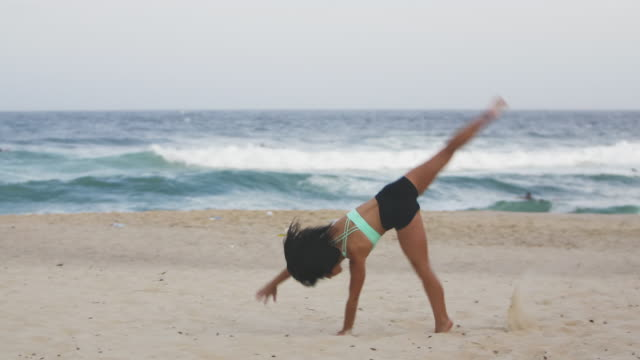 Beautiful yoga girl does cartwheel on the beach (slow motion)