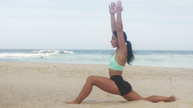 beautiful yoga girl stretches on the beach - acrobatic activity stock videos and b-roll footage