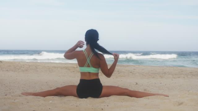 vídeos de stock, filmes e b-roll de menina bonita de ioga estende-se na praia - praia de bondi