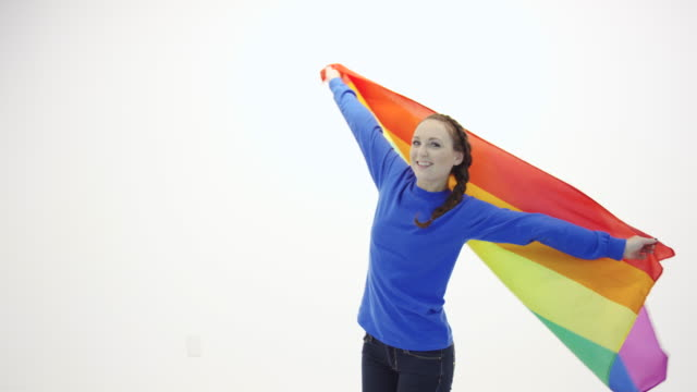 Beautiful young adult female spinning holding gay pride flag