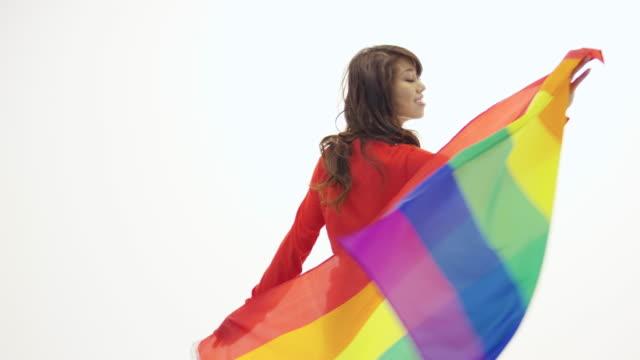 ゲイプライド旗を保持して回転美しい若い成人女性 - ジェンダー・ステレオタイプ点の映像素材/bロール
