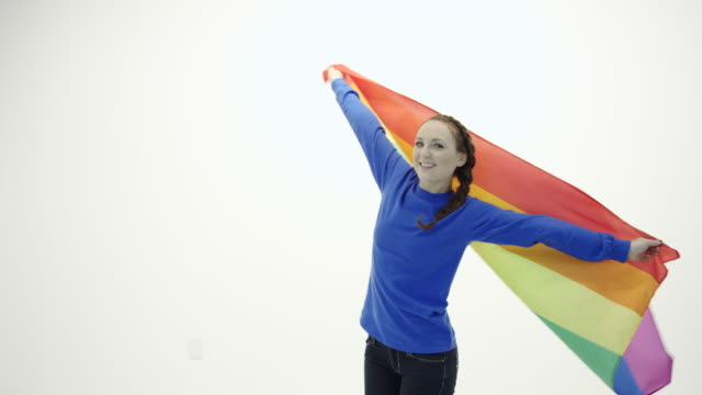 Beautiful young adult female spinning in circle with gay pride flag
