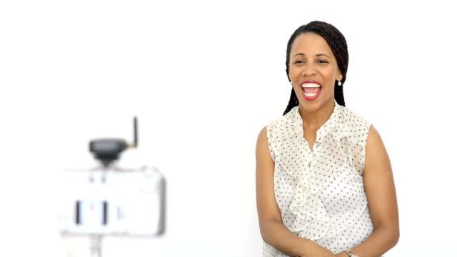 vídeos de stock, filmes e b-roll de mulher nova bonita do americano africano no fundo branco que fala e que sorri ao vídeo do estoque da câmera - câmera de conferência