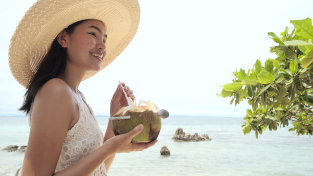 beautiful young asia woman drink a coconut water along on the beach. - coconut stock videos & royalty-free footage