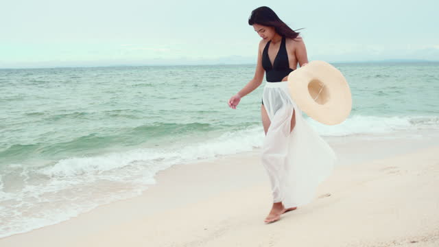 beautiful young asia woman walking along on the beach. - human limb stock videos & royalty-free footage