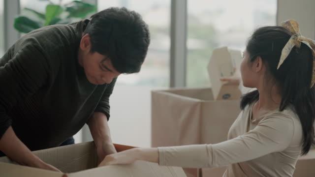 美しい若いアジアのカップルは、新しいアパートで一緒に自分のものを開梱 - 引っ越し点の映像素材/bロール