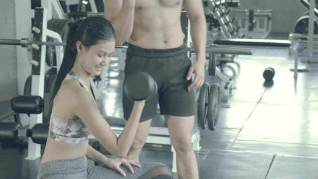 beautiful young asian woman and coach training workout with strong at gym, asia man teach girl bodyweight with lifting dumbbell at fitness, female strength with exercise, wellbeing and healthy concept. - bodyweight training stock videos & royalty-free footage
