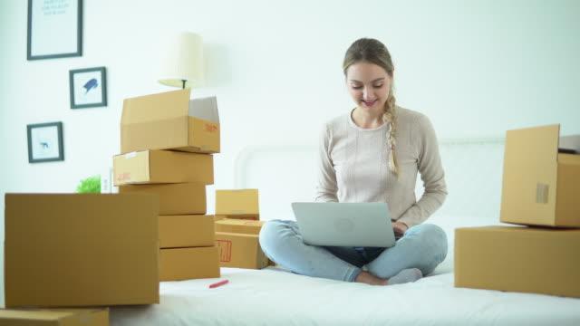 vídeos de stock, filmes e b-roll de mulher asiática nova bonita em casa trabalhador em linha que escaneia o pacote - pacote arranjo