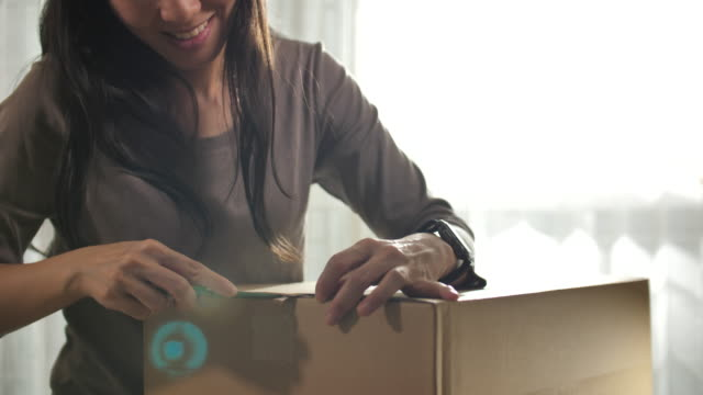 beautiful young asian woman at home opens cardboard box while standing on her desk in her bright living room, online delivery - mail stock videos & royalty-free footage