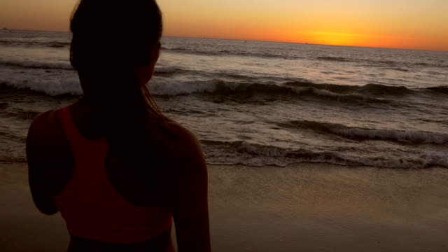 beautiful young asian woman gazing at sunset on sandy beach after running - sports bra stock videos & royalty-free footage