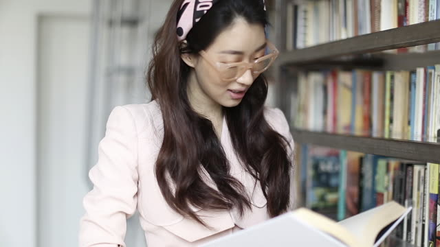 beautiful young asian woman happily reading a book - reading glasses stock videos & royalty-free footage