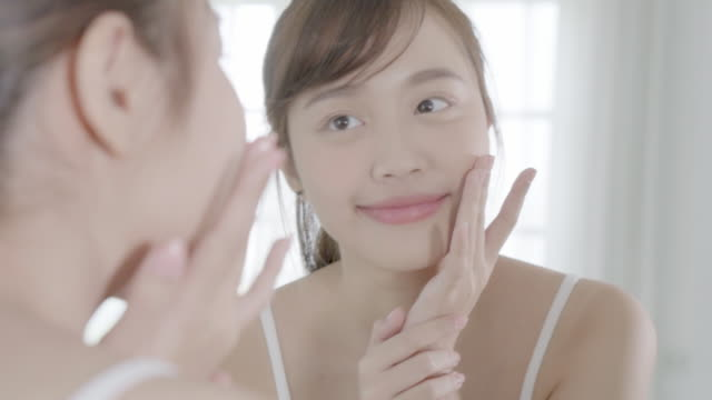 vídeos de stock e filmes b-roll de beautiful young asian woman happy applying cream or lotion with moisturizer to skin face, beauty asia girl applying skincare touch facial with cosmetic makeup, healthy and wellness concept. - spa treatment
