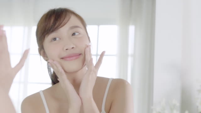 beautiful young asian woman happy applying cream or lotion with moisturizer to skin face, beauty asia girl applying skincare touch facial with cosmetic makeup, healthy and wellness concept. - skin care stock videos & royalty-free footage